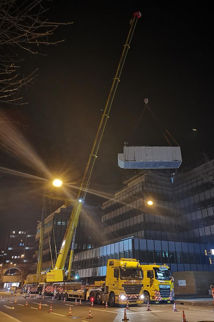 Heben der Notstromgruppe mit dem Mobilkran an ihren neuen Standort auf dem Gebäude der Zürcher Kantonalbank
